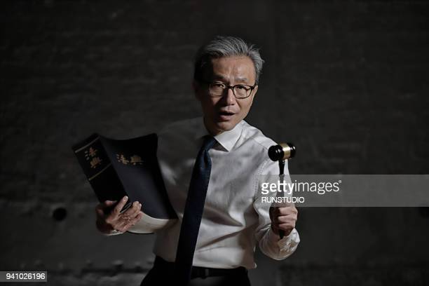 lawyer holding gavel with law book - legal trial stock pictures, royalty-free photos & images