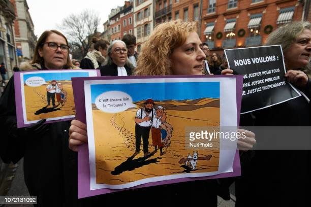 A lawyer holds a drawing of Tintin reading 'Its stiil far away the courthouse' Lawyers counsels and magistrates gathered in front of the Toulouse'...