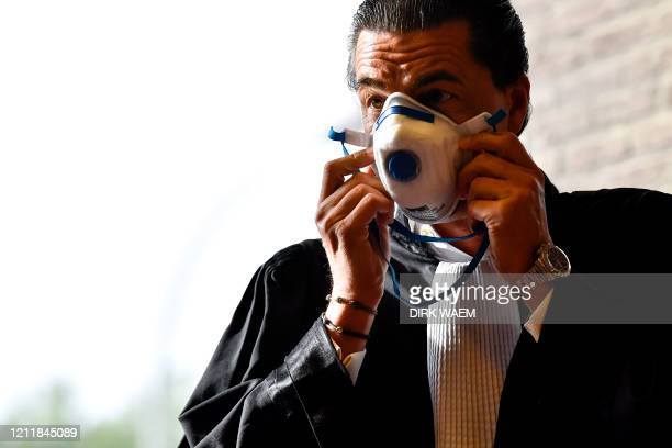 Lawyer Kris Luyckx puts on a mouth mask at the start of a session of the assize trial of five accused for the robbery homicide on Leopoldine De...
