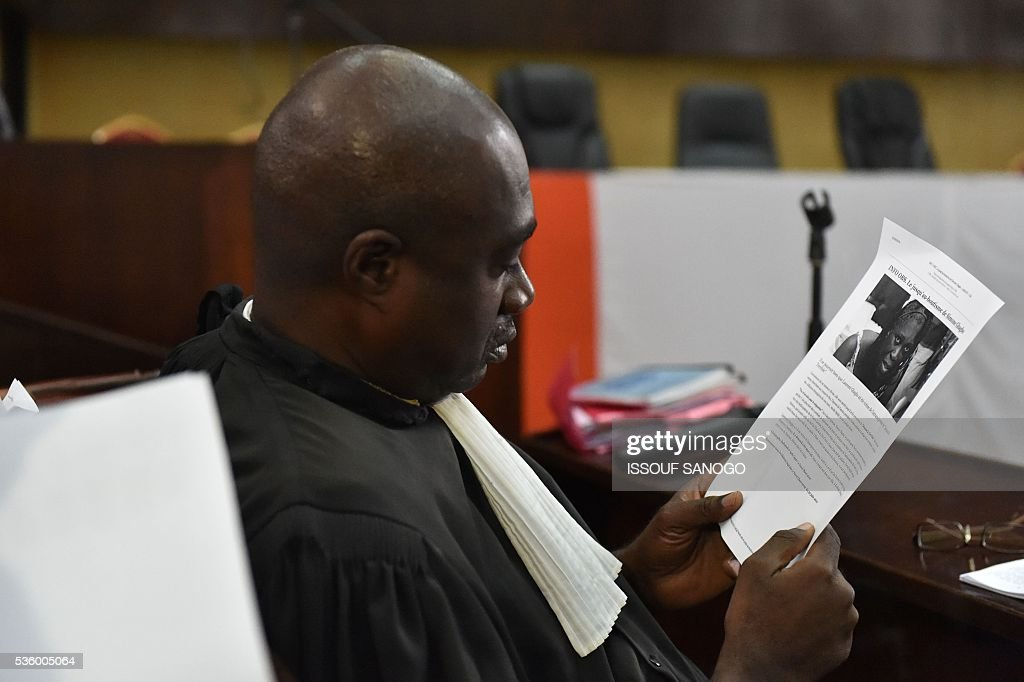 A lawyer of Ivory Coast's former first lady attends with documents during her trial on May 31, at the Abidjan Justice Court. Simone Gbagbo goes on trial for crimes against humanity in what many see as a litmus case for justice in the West African country. The hearings into the 66-year-old's role in post-election carnage in 2010 is expected to last a month with 32 witnesses testifying. SANOGO