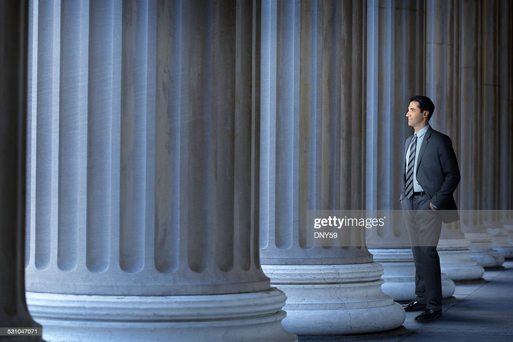 Lawyer Or Banker Standing Next To Large Columns : Stock Photo