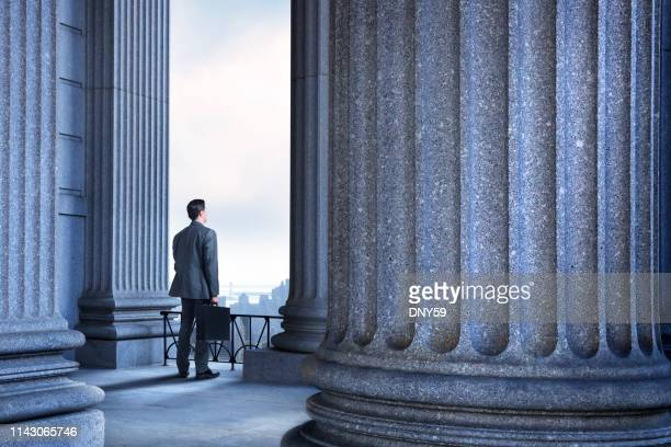 lawyer or businessman standing in portico of greek columns - legal system stock pictures, royalty-free photos & images
