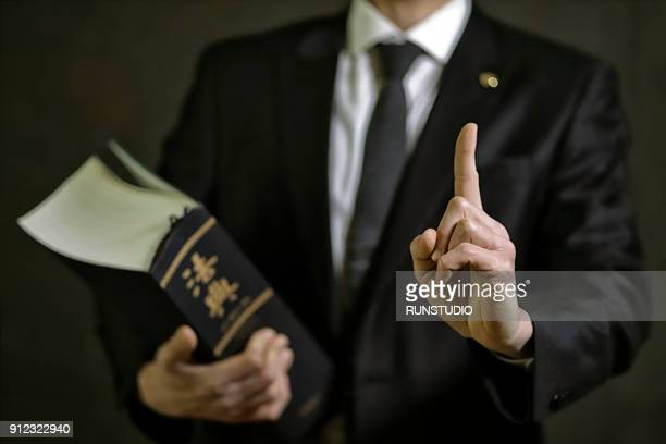 lawyer pointing finger with law book - 弁護士 ストックフォトと画像