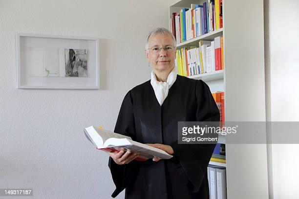 lawyer reading text book in office - sigrid gombert stock-fotos und bilder