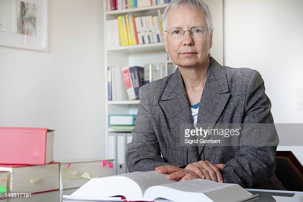 lawyer reading text book in office - sigrid gombert stock pictures, royalty-free photos & images