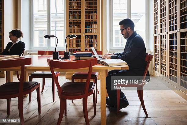 Lawyer researching on laptop while sitting in library