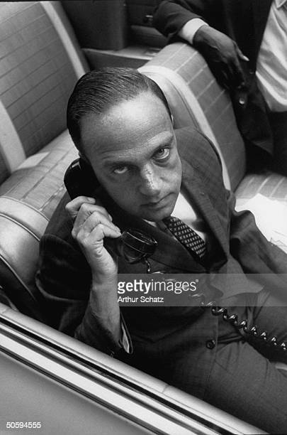 Lawyer Roy Cohn sitting in front seat of his 1961 Chevrolet Impala convertible talking on telephone with client he is parked in front of his Madison...