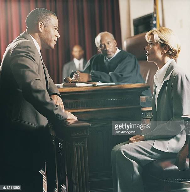 lawyer standing questioning witness in courtroom - witness stock pictures, royalty-free photos & images