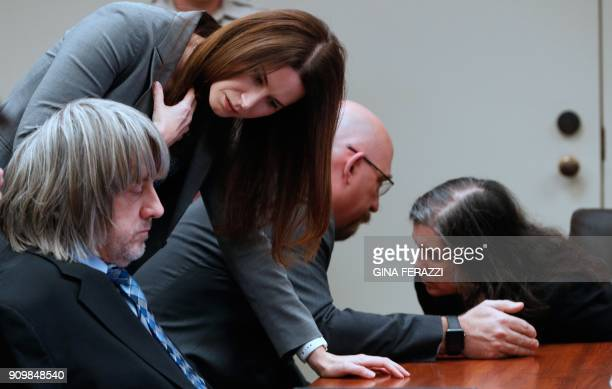 Lawyers Allison Lowe and Jeff Moore speak with David and Louise Turpin in court on January 24 2018 in Riverside California David Allen Turpin and his...