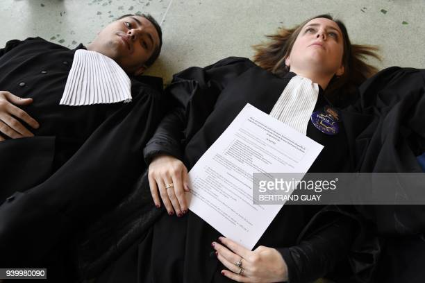 Lawyers and magistrates lay on the ground at the entrance hall of the Courthouse in Nanterre outside Paris on March 30 as part of a nation wide day...