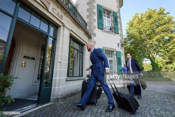 Lawyers arrive at the Court of Arbitration for Sport in Lausanne on July 19 for an appeal by AC Milan against a European ban for breaking UEFA's...