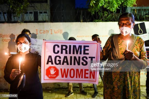 Lawyers display a placard to condemn the alleged gang-rape and murder of a low-caste teenaged woman in Uttar Pradesh state during a candlelight vigil...