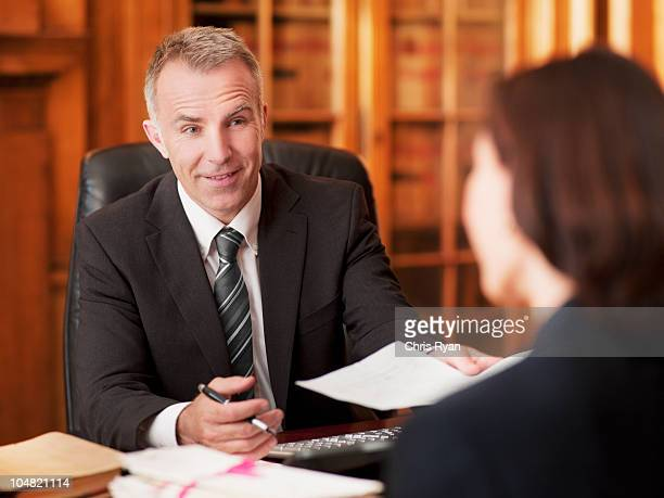 lawyers exchanging paperwork in office - law office stock photos and pictures