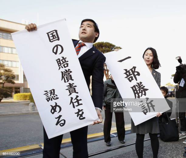 Lawyers for plaintiffs hold banners on March 17 in front of the Maebashi District Court, north of Tokyo, after it ruled negligence by the central...