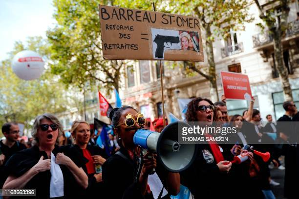 """Lawyers from Saint Omer bar hold a placard reading """"Pensions reform"""" past a gun as they protest against the pension reform in Paris on September 16,..."""