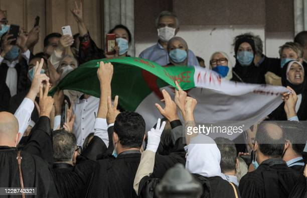 Lawyers, mask-clad due to the COVID-19 coronavirus pandemic, chant slogans and wave an Algerian national flag as they demonstrate outside the Court...