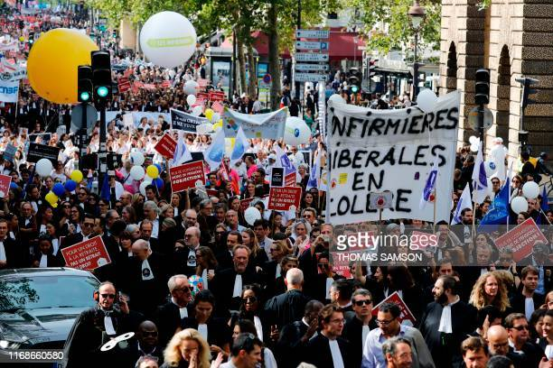 Lawyers nurses and other professionals hold banners and placards as they protest against the pension reform in Paris on September 16 2019 Several...