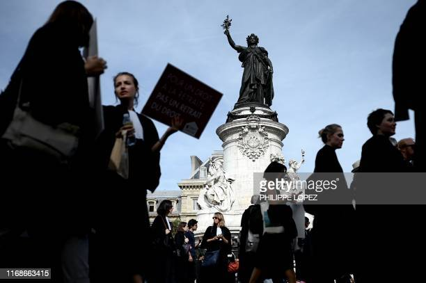 Lawyers pass by the statue of Republic Square as they protest against the pension reform in Paris on September 16 2019 Several thousand lawyers...