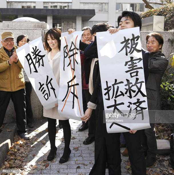 Lawyers representing two chronic hepatitis B sufferers in a lawsuit over reduced state benefit for relapse cases hold up signs in front of the...