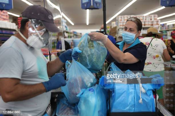 Lay Guzman stands behind a partial protective plastic screen and wears a mask and gloves as she works as a cashier at the Presidente Supermarket on...