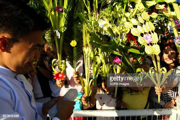 CHURCH ANTIPOLO RIZAL PHILIPPINES A lay minister blesses the palm fronds of devotees with holy water outside the Antipolo church Rizal province east...
