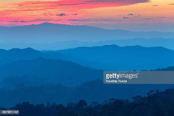 Layer of mountains in the mist at sunset time with burning sky, Nan Province, Thailand