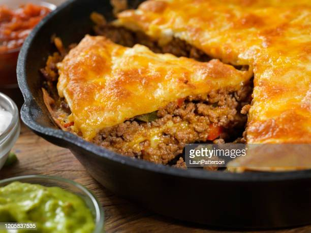 layered, beef taco pie baked in a cast iron skillet with sour cream, salsa and guacamole - comfort food stock pictures, royalty-free photos & images