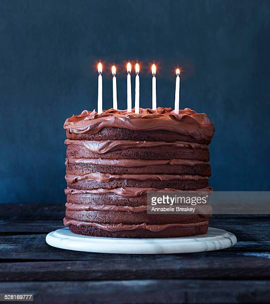 layered chocolate birthday cake with candles - birthday cake stock photos and pictures