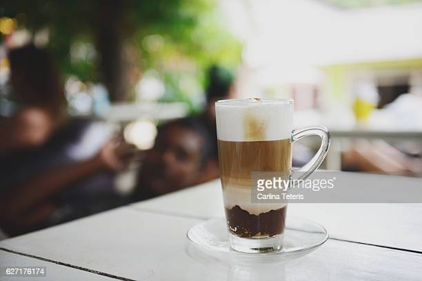 Layered mocha on a table in an outdoor cafe
