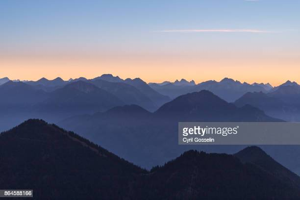 layered mountain summits emerging from thin mist at dusk - dämmerung stock pictures, royalty-free photos & images