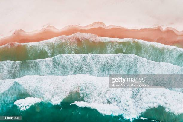 layered pattern of waves on beach. - nazar abbas photography stock pictures, royalty-free photos & images