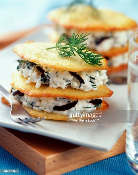 Layered thin cheese biscuits and fromage frais with olives