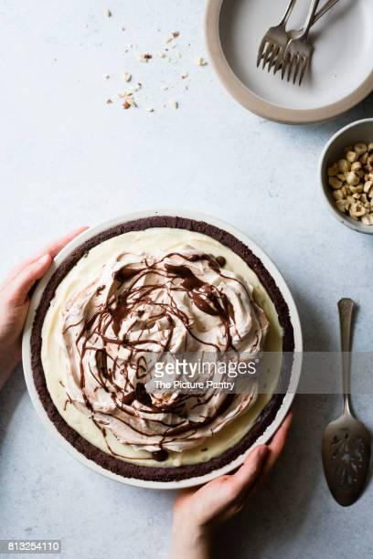 A layered triple chocolate pie in a womans hands