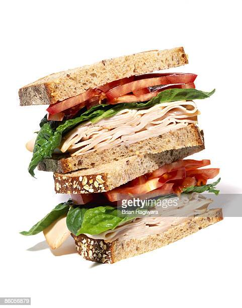layered turkey sandwich with lettuce and tomato - sandwich stock pictures, royalty-free photos & images