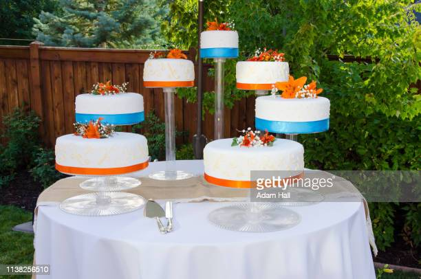 layers white wedding cake on stands on a table  with orange flowers, blue ribbons and orange ribbons - utah wedding stock pictures, royalty-free photos & images