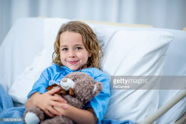 laying with teddy bear - hospital stock pictures, royalty-free photos & images