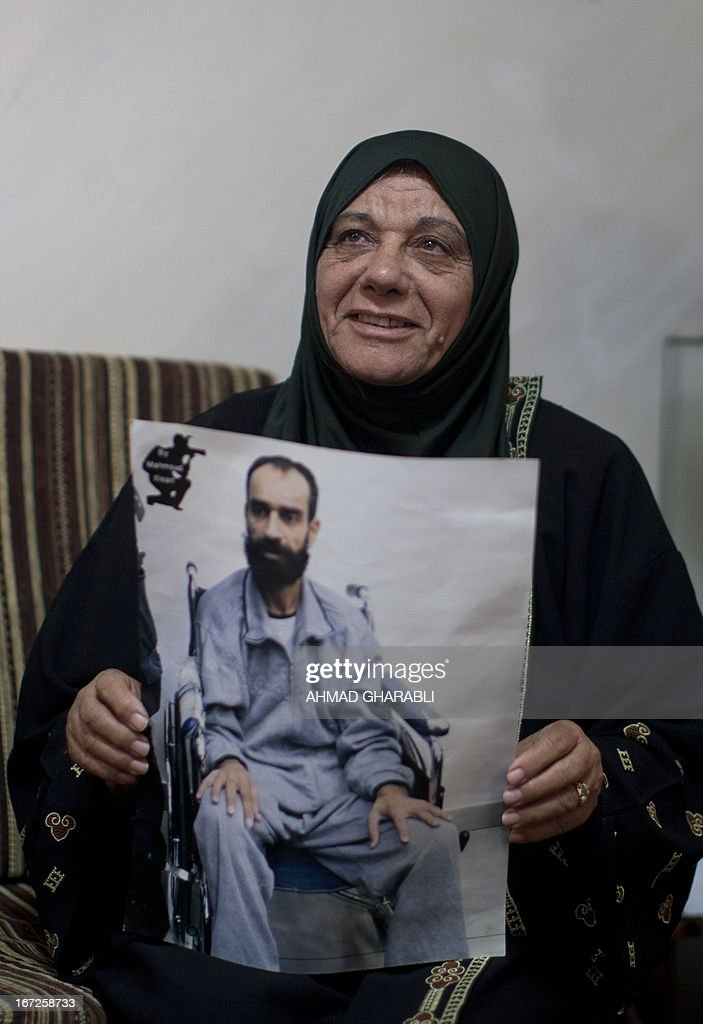 Layla Issawi holds a picture of her son Samer who has been on hunger strike for 260 days while being held in an Israeli prison, as she celebrates a deal for his release at their home in the East Jerusalem neighbourhood of Issawiya on April 23, 2013. Issawi has agreed to end his protest in return for his release, his lawyer said.