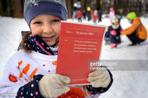 Layla poses on January 18, 2021 in Lausanne with voting material identical to what Swiss citizen receive before each popular vote during a...