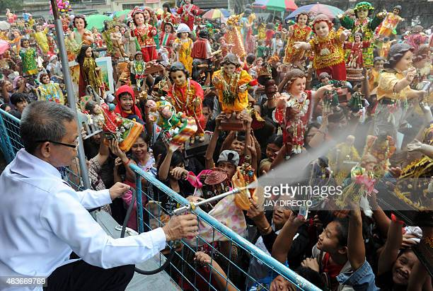A layman uses a spray to hose holy water to bless religious icons of the baby Jesus as thousands of residents of Manila's Tondo district carry small...