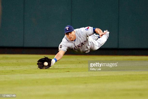 Laynce Nix of the Texas Rangers makes an unsuccessful diving catch of a fly ball by Adam Kennedy of the Los Angeles Angels of Anaheim in the fourth...