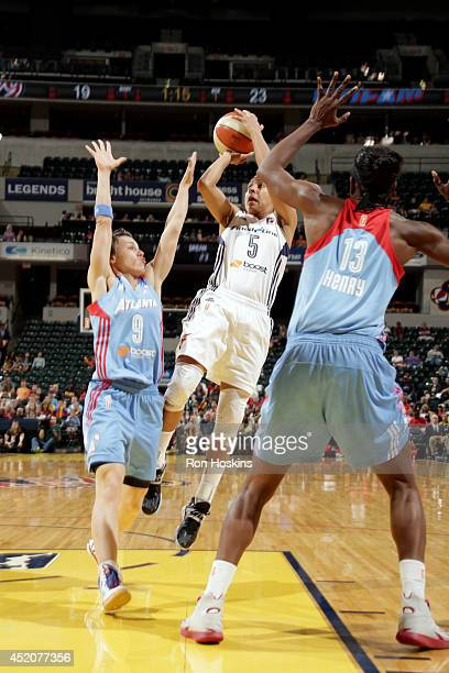 Layshia Clarendon of the Indiana Fever shoots against Celine Dumerc of the Atlanta Dream and Aneika Henry of the Atlanta Dream on July 12 2014 at...