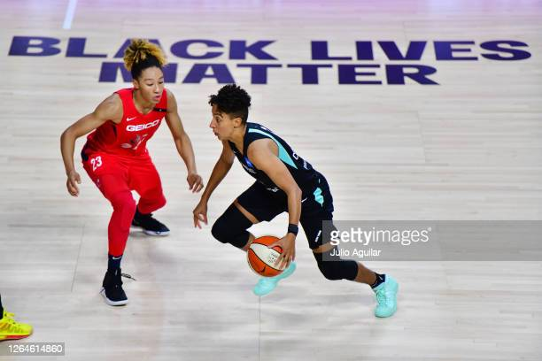 Layshia Clarendon of the New York Liberty is guarded by Aerial Powers of the Washington Mystics in front of a Black Lives Matter graphic on court...