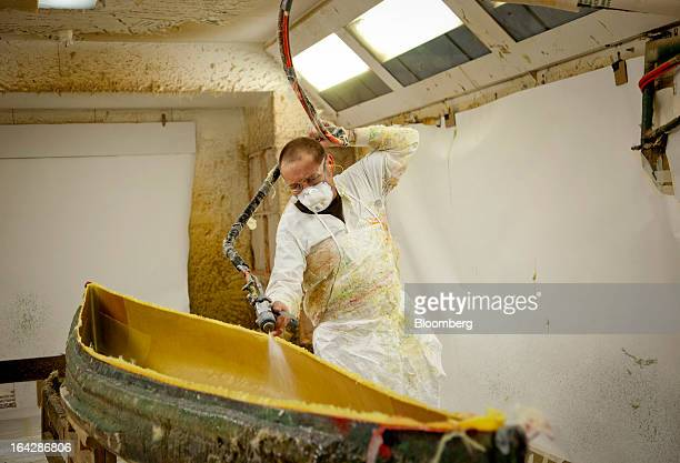 Layup supervisor Roy Pelowski sprays vinyl ester resin onto Kevlar fabric in a mold used to make a Prism canoe at the Wenonah Canoe factory in Winona...