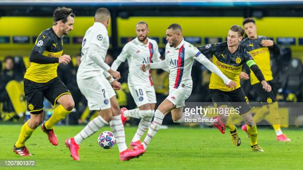Layvin Kurzawa of Paris SaintGermain is challenged by Lukasz Piszczek of Borussia Dortmund during the UEFA Champions League round of 16 first leg...