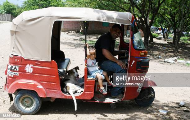 Lazaro Villalobos who was deported from the United States leaving his wife and two children behind drives his red motorcycle taxi along the dusty...