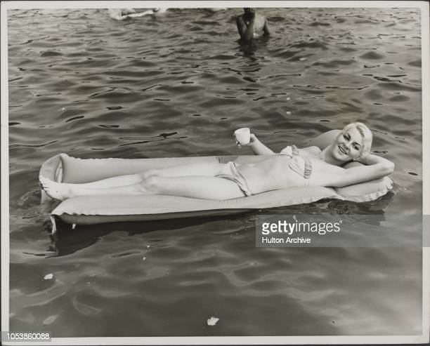 Lazing in the sun on the Serpentine, Photograph shows Keeping cool on an air-bed on the Serpentine, is twenty one year old 'BOBBIE' ROSENBERG, of...