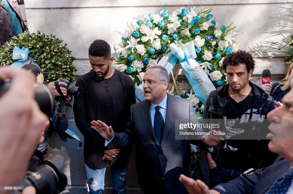 Lazio Chairman Claudio Lotito (C) and a delegation including players Wallace (S) and Felipe Anderson (R) lay flowers at Rome's synagogue after a group of the club's ultras of Lazio used Anti-Semitic stickers with the image of Anne Frank wearing a Roma shirt to insult followers of city rivals AS Roma on October 24, 2017 in Rome, Italy. The stickers and anti-Semitic slurs were found on glass barriers, walls and bathrooms in a section of Rome's Olympic Stadium that was used by Lazio supporters on Sunday in their Serie A match against Cagliari.