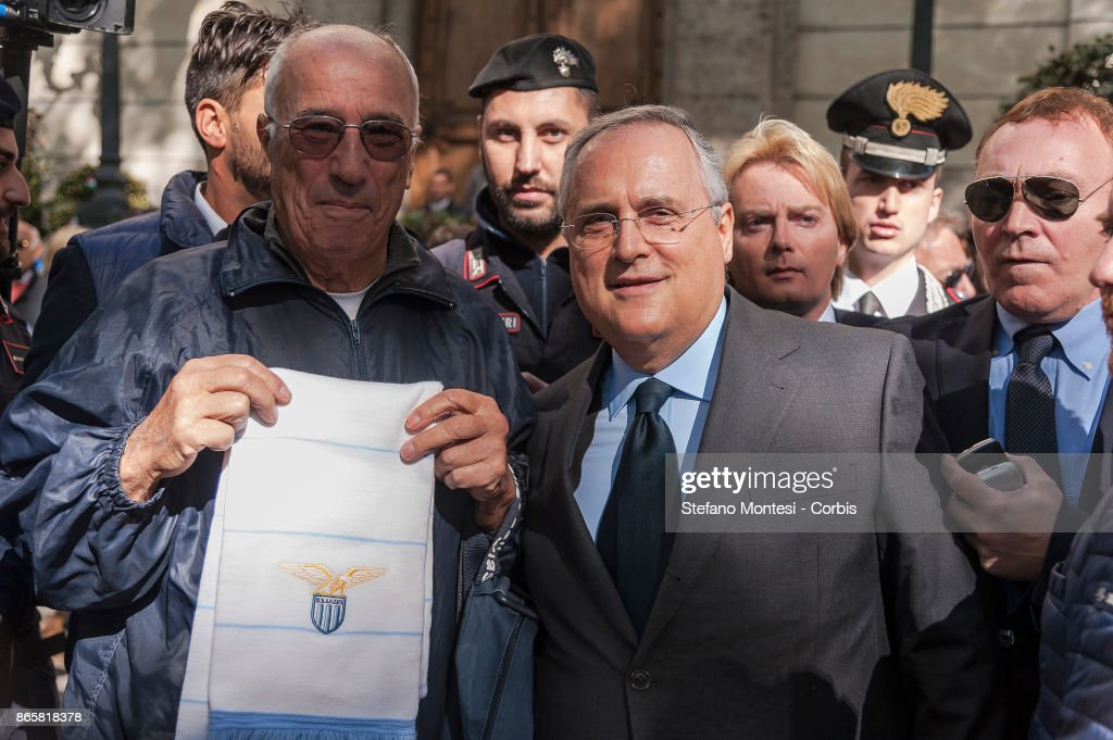 A Lazio fan in front of the synagogue attend with Lazio Chairman Claudio Lotito (C) and a delegation including players Wallace and Felipe Anderson lay flowers at Rome's synagogue after a group of the club's ultras of Lazio used Anti-Semitic stickers with the image of Anne Frank wearing a Roma shirt to insult followers of city rivals AS Roma on October 24, 2017 in Rome, Italy. The stickers and anti-Semitic slurs were found on glass barriers, walls and bathrooms in a section of Rome's Olympic Stadium that was used by Lazio supporters on Sunday in their Serie A match against Cagliari.