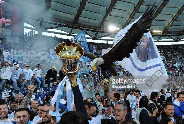 Lazio mascot Olimpia, a female American golden eagle, is held with Tim Cup after the TIM cup final match between AS Roma v SS Lazio at Stadio...