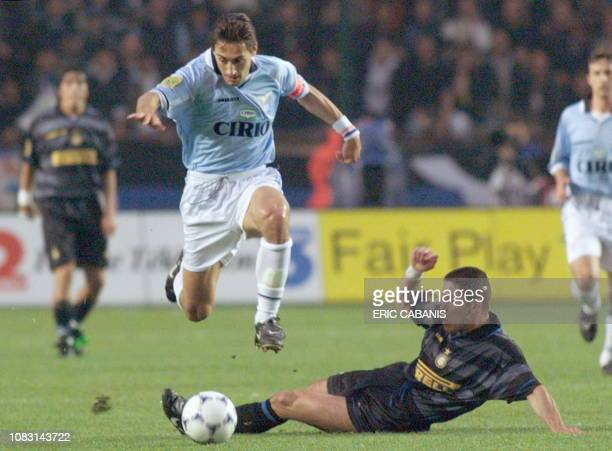 Lazio Rome's captain Diego Fuser jumps over the attempted tackle of Inter Milan's Diego Simeone 06 May at the Parc des Princes Stadium in Paris...